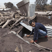 "Bryan Rivera sifts through the remains of his house, after his family went missing during the Volcan de Fuego or ""Volcano of Fire"" eruption, in San Miguel Los Lotes, Guatemala, on June 7. (AP Photo/Moisés Castillo)"