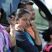 Friends, coworkers and family watch as U.S. immigration officials raid the Koch Foods Inc., plant in Morton, Miss., Wednesday, Aug. 7, 2019. U.S. immigration officials raided several Mississippi food processing plants on Wednesday and signaled that the early-morning strikes were part of a large-scale operation targeting owners as well as employees. (AP Photo/Rogelio V. Solis)