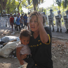 A female migrant carrying a child moves away from Mexican National Guards blocking the passage of a group of Central American migrants near Tapachula, Mexico, Thursday, Jan. 23, 2020. Hundreds of Central American migrants crossed the Suchiate River into Mexico from Guatemala Thursday after a days-long standoff with security forces. (AP Photo/Marco Ugarte)