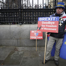 Anti-Brexit campaigner Steve Bray holds banners as he stands outside Parliament in London on Jan. 30, 2020. Although Britain formally leaves the European Union on Jan. 31, little will change until the end of the year. (AP Photo/Kirsty Wigglesworth)