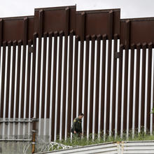 A border patrol agent walks along a wall separating Tijuana, Mexico, from San Diego on March 18. (AP Photo/Gregory Bull)
