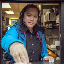 Milagrose Sarmiento works the drive-through window at a McDonald's restaurant in Sitka, Alaska, on April 24. Low-paid workers such as restaurant employees are proving their value during the coronavirus pandemic. (James Poulson/The Daily Sitka Sentinel via AP)
