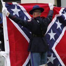 A Mississippi Highway Safety Patrol honor guard folds the retired Mississippi state flag after it was raised over the Capitol grounds one final time in Jackson, Miss., on July 1. (AP Photo/Rogelio V. Solis)
