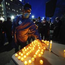 Health service workers light candles during a vigil for coronavirus victims at Elmhurst Hospital in Queens, New York, on April 16. (Photo by John Nacion/STAR MAX/IPx 2020)