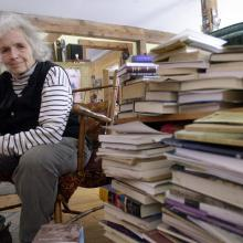 Grace Paley sits beside a pile of books in her home in Thetford Hill, Vt., April 9, 2003(AP Photo/Toby Talbot).