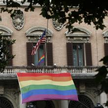 Rainbow flags fly alongside the U.S. flag outside the U.S. Embassy to Italy in Rome June 16. A prayer service was held nearby at St. Patrick's Catholic Church in remembrance of the victims of the Orlando, Fla., terrorist attack(CNS photo/Paul Haring).