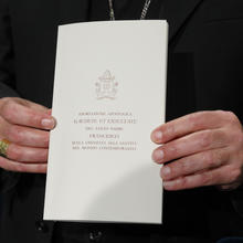 "Archbishop Angelo De Donatis, papal vicar for the Diocese of Rome, holds a copy of Pope Francis' exhortation, ""Gaudete et Exsultate"" (""Rejoice and Be Glad""), during a news conference on the exhortation at the Vatican April 9. (CNS photo/Paul Haring)"