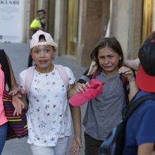 Children, some in tears, are escorted down a road in Barcelona, Spain, Thursday, Aug. 17, 2017. Police in Barcelona say a white van has mounted a sidewalk, struck several people in the city's Las Ramblas district. (AP Photo/Manu Fernandez)