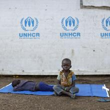 In this Friday, June 9, 2017 file photo, a South Sudanese refugee boy sits on a mat outside a communal tent while his brother sleeps, at the Imvepi reception center, where newly arrived refugees are processed before being allocated plots of land in nearby Bidi Bidi refugee settlement, in northern Uganda. AP Photo/Ben Curtis, File)