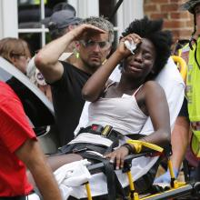Rescue personnel help an injured woman after a car ran into a large group of protesters after an white nationalist rally in Charlottesville, Va., onAug. 12. (AP Photo/Steve Helber)