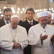 Pope Francis prays with Istanbul's grand mufti Rahmi Yaran during a visit to the Sultan Ahmed Mosque, also known as the Blue Mosque, in Istanbul Nov. 29. (CNS photo/L'Osservatore Romano via Reuters)