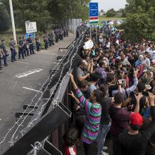 Migrants stand in front of a barrier at the border with Hungary near the village of Horgos, Serbia, on Sept. 16, 2015. (Photo courtesy of Reuters/Marko Djurica)