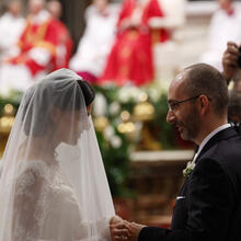 New spouses exchange rings as Pope Francis, pictured in the background, celebrates the marriage rite for 20 couples during a Mass in St. Peter's Basilica at the Vatican on Sept. 14. (CNS photo/Paul Haring)