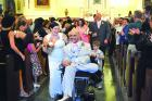HOLY UNION. After extricating the train of her wedding dress from her husband's wheelchair, Amanda and Andres Gonzalez process down the aisle in Our Lady of Guadalupe Church of New Orleans.