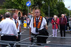 A member of the Orange Order looks on July 12, 2016, at a temporary blockade put in place by police during the order's annual parade in Belfast, Northern Ireland. Loyalists were commemorating the 1690 defeat of the Catholic King James II by the Protestant Prince William of Orange. (CNS photo/Clodagh Kilcoyne, Reuters)