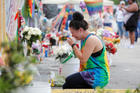 A woman cries while visiting the memorial outside the Pulse nightclub in Orlando, Fla., June 12, the one year anniversary of the mass shooting. The Diocese of Orlando broadcast via Facebook Live a prayer service attended by clergy of various faiths to remember the 49 who died June 12, 2016, during the largest mass shooting by a single gunman in the country's history. (CNS photo/Scott Audette, Reuters)