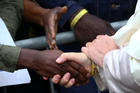 Pope Francis shakes hands with a man as he visits a migrant reception centre during a pastoral visit in Bologna, Italy, Oct. 1. The pope is seen wearing a yellow ID bracelet with his name and a number, just like the immigrants and refugees at the center. (CNS photo/Alessandro Bianchi, Reuters)