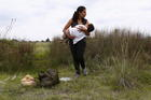 A Salvadoran immigrant carries her son in a field in Huehuetoca, Mexico, while trying to reach the U.S.-Mexico border in 2015. (CNS photo/Edgard Garrido, Reuters)