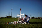 Joe Zevuloni weeps in front of a cross placed in a park to commemorate the victims of the shooting at nearby Marjory Stoneman Douglas High School in Parkland, Fla., on Feb. 16.At least 17 people were killed in the Feb. 14 shooting. (CNS photo/Carlos Garcia Rawlins, Reuters)