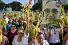 Worshippers wave palm fronds near an image of Blessed Oscar Romero during a Palm Sunday procession March 25 in San Salvador, El Salvador. Catholic officials in El Salvador were shaken and expressed outrage and sadness after the assassination of a 36-year-old priest during Holy Week, in what some suspect may be a gang killing. (CNS photo/Armando Escobar, EPA)
