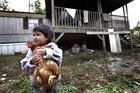 A boy holds a family chicken outside his home in Steele, Ala., in this 2013 file photo. (CNS photo/Karen Callaway, Catholic New World)