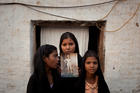 The daughters of Asia Bibi pose in 2010 with an image of their mother outside their residence in Sheikhupura, Pakistan. (CNS photo/Adrees Latif, Reuters)