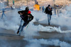 Palestinian demonstrators run away from tear gas fired by Israeli forces on Nov. 16, during an anti-Israel protest near the Jewish settlement of Beit El in the Israeli-occupied West Bank. (CNS photo/Mohamad Torokman, Reuters)