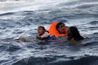 A boy cries out for help as a half-sunken catamaran carrying around 150 refugees, most of them Syrians, arrives at the Greek island of Lesbos, Oct. 30, 2015. Turkey and Greece are trading blame following the deaths of Syrian refugees trying to flee to Europe. (CNS photo/Giorgos Moutafis, Reuters)