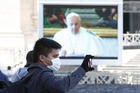 A man wearing a mask takes a photo as Pope Francis appears on a video monitor in St. Peter's Square as he leads the Angelus from his library in the Apostolic Palace at the Vatican March 8, 2020. (CNS photo/Paul Haring)