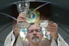 A priest raises the chalice andCommunionhost in this illustration. (CNS photo/Bob Roller)