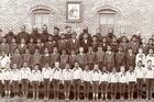 Jesuits and boys under picture of St. Ignatius at the Holy Rosary Mission circa 1880-1900. Courtesy of Marquette University, Raynor Memorial Libraries and Holy Rosary Mission–Red Cloud Indian School Records,ID:MUA_HRM_RCIS_02937.