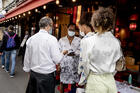 Women show their health passes to a waiter in Paris on Aug. 19, 2021. France, Italy, Denmark and the U.S. cities of New York, San Francisco and New Orleans are among the places that have imposed vaccination requirements at places like restaurants, gyms and theaters as the Delta variant of Covid-19 spreads. (AP Photo/Adrienne Surprenant)