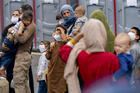 People evacuated from Afghanistan step off a bus as they arrive at a processing center.