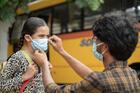 A man fixes a young girl's face mask