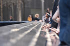 Visitors touch the names engraved in the 9/11 Memorial in Manhattan.
