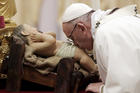Pope Francis kisses a statue of Baby Jesus as he celebrates the Christmas Eve Mass in St. Peter's Basilica at the Vatican, Sunday, Dec. 24, 2017. (AP Photo/Alessandra Tarantino)