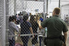A U.S. Border Patrol agent watches as people who've been taken into custody related to cases of illegal entry into the United States, stand in line at a facility in McAllen, Texas, Sunday, June 17, 2018. (U.S. Customs and Border Protection's Rio Grande Valley Sector via AP)