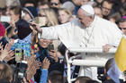 Pope Francis caresses a child as he arrives to celebrate a Mass in Freedom Square, in Tallinn, Estonia, Tuesday, Sept. 25, 2018. (AP Photo/Mindaugas Kulbis)