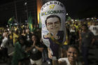 A supporter holds a balloon with the image of presidential candidate Jair Bolsonaro, during celebration in front of the National Congress, in Brasilia, Brazil, on Oct. 28. (AP Photo/Eraldo Peres)