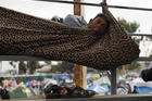 A migrant rests inside a blanket tied to keep him from rolling off the spectator stands at the Benito Juárez Sports Complex in Tijuana, Mexico. (AP Photo/Rebecca Blackwell)