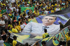 On Jan 1, supporters of Brazil's new President Jair Bolsonaro display a giant banner of him on his inauguration day in Brasilia, Brazil. (AP Photo/Silvia Izquierdo)