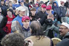 """On Jan. 18, a teenager wearing a """"Make America Great Again"""" hat, center left, stands in front of an elderly Native American singing and playing a drum in Washington. (Survival Media Agency via AP)"""
