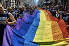 Revelers carry a rainbow flag along Fifth Avenue during the L.G.B.T. Pride Parade in New York on June 24, 2018. (AP Photo/Andres Kudacki, File)