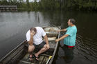 Stephen Gilbert, left, and his father-in-law sit in front of their flooded property on Sept. 20 in the Mauriceville, Texas, area. Floodwaters are starting to recede in most of the Houston area after the remnants of Tropical Storm Imelda flooded parts of Texas. Imelda will likely be Southeast Texas' fifth 500-year flood event in as many years. ( Jon Shapley/Houston Chronicle via AP)