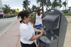 Maria Gomez, foreground, washes her hands at a public sink in Miami Beach, Fla., on June 22. (AP Photo/Wilfredo Lee)