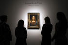 People gather around Leonardo da Vinci's 'Salvator Mundi' on display at Christie's auction rooms, in London, Tuesday, Oct. 24 (AP Photo/Kirsty Wigglesworth).