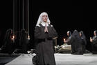 Nun kneeling on stage