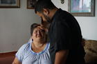Father Carlos Francis Mendez visits with Rosa Mendez Torres, a woman who suffers from diabetes, in Las Marias, Puerto Rico. (J.D. Long-García)
