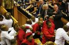 "Economic Freedom Fighters in red are forcibly removed from parliament in Cape Town, South Africa, on Feb. 9, 2017. Parliament descended into chaos with opposition lawmakers denouncing President Jacob Zuma as a ""scoundrel"" and ""rotten to the core"" because of corruption allegations and then brawling with guards who dragged them out of the chamber. (AP Photo/Sumaya Hisham, Pool)"