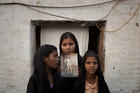 Asia Bibi's daughters hold up a picture of their mother